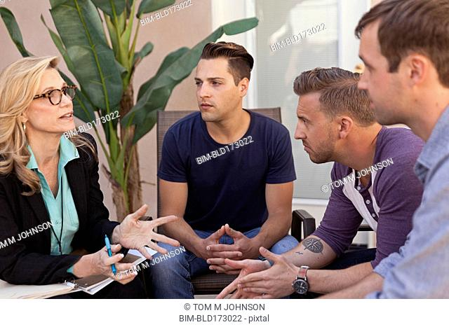 Men talking with therapist in group therapy