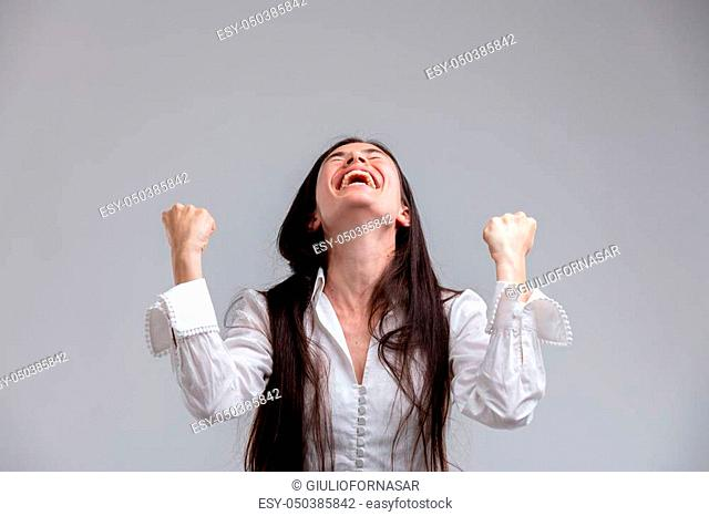 Jubilant woman laughing and clenching her fists punching the air as she celebrates a success or victory over grey