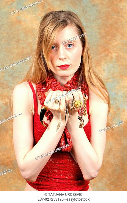 Young beautiful girl in red holding fancy gold jewelry