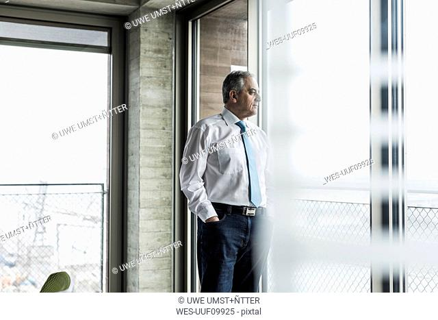 Senior manager in office standing at the window