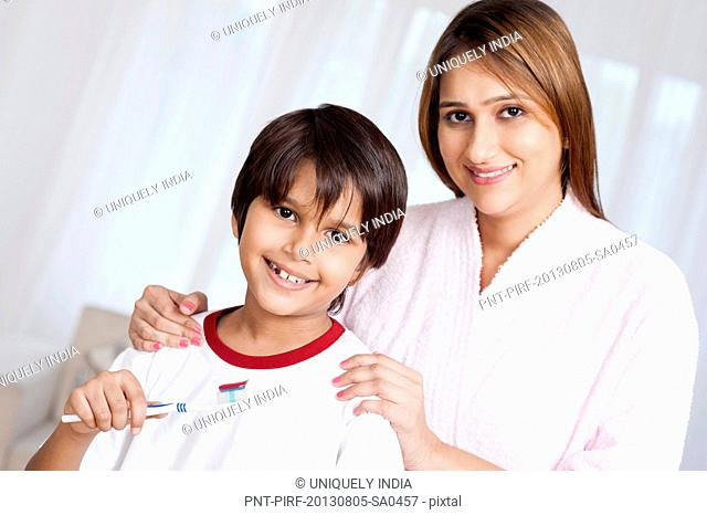 Portrait of a woman smiling with her son holding a toothbrush