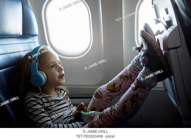 Girl wearing headphones on airplane