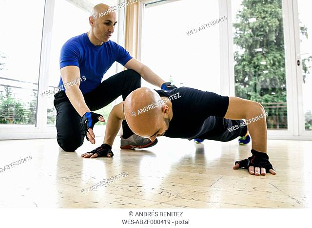 Man doing push-ups assisted by a trainer