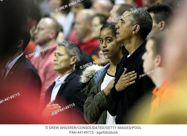 (L-R): daughter Malia Obama and United States President Barack Obama stand during the National Anthem before the men's NCAA basketball match between University...
