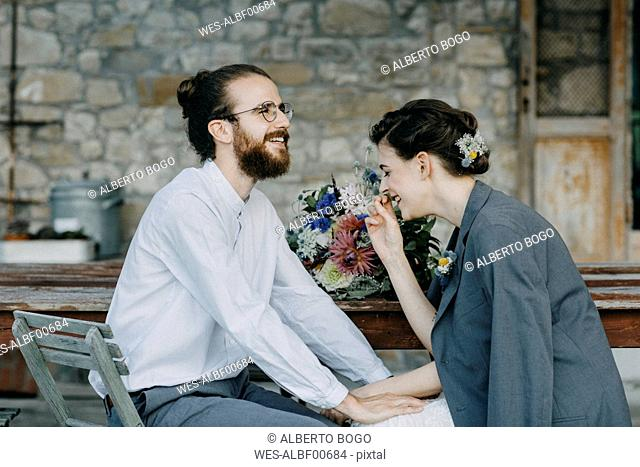 Happy bride and groom sitting at table