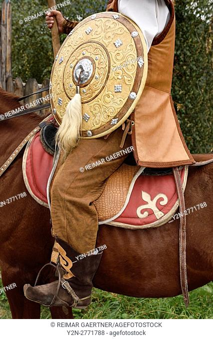 Detail of guard in traditional hun clothes with shield and spear on horseback Kazakhstan