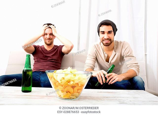 Two Friends watching passionately TV with Beer and Chips