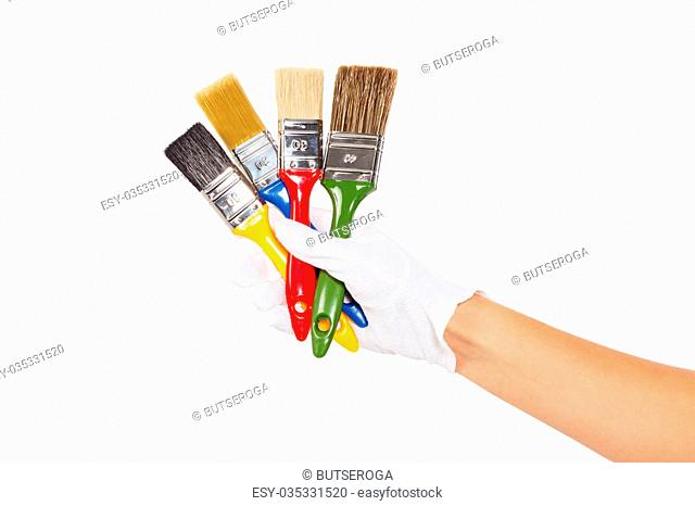 Woman's hand in white glove with colorful paintbrushes