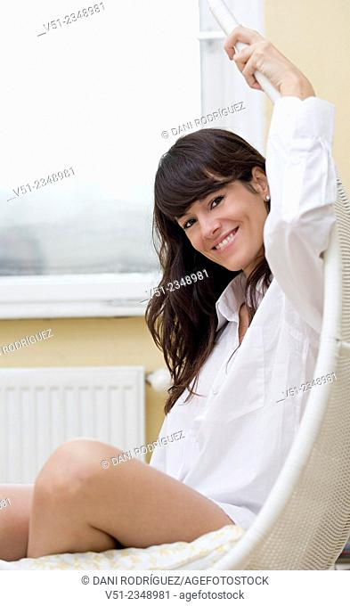 Woman in bedroom sitting in a hammock smiling at camera
