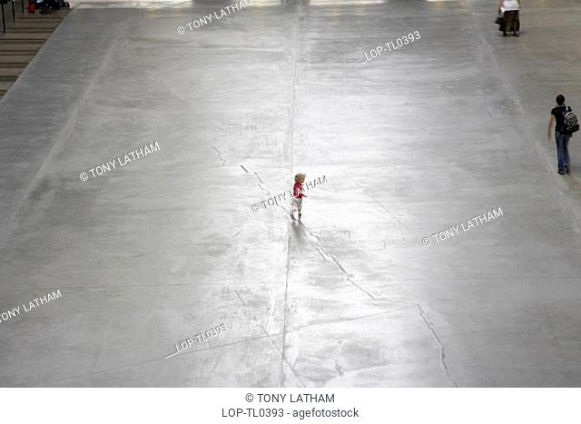 England, London, South Bank, A small child playing in the Turbine Hall of the Tate Modern