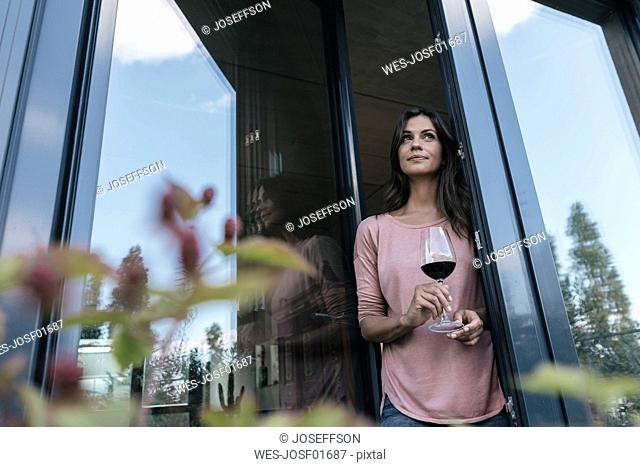 Woman holding glass of red wine looking out of window