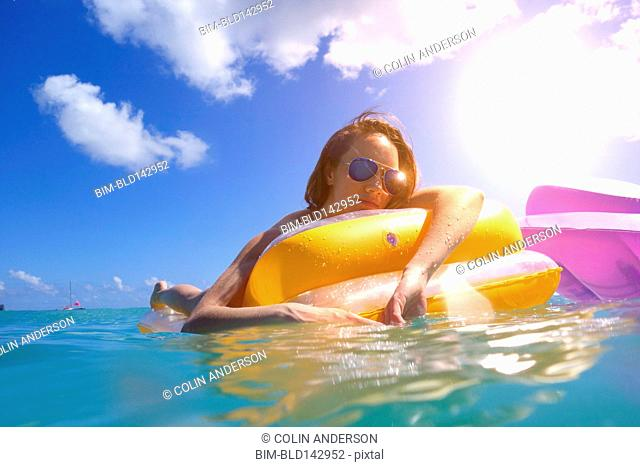Pacific Islander woman floating on inflatable raft