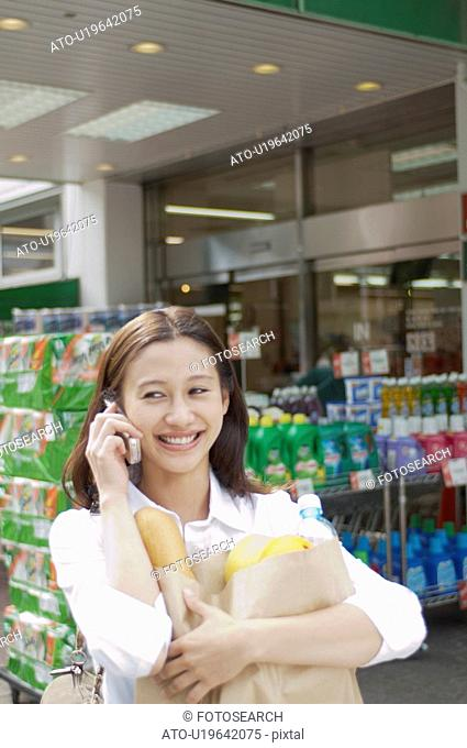 Young Woman Talking on Cellular Phone in Front of Supermarket