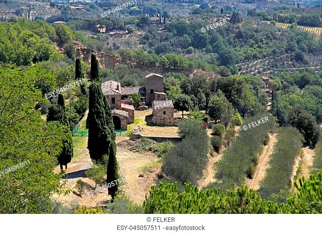 Beautiful landscape view with old buildings, trees and meadows near Montepulciano town, Italy