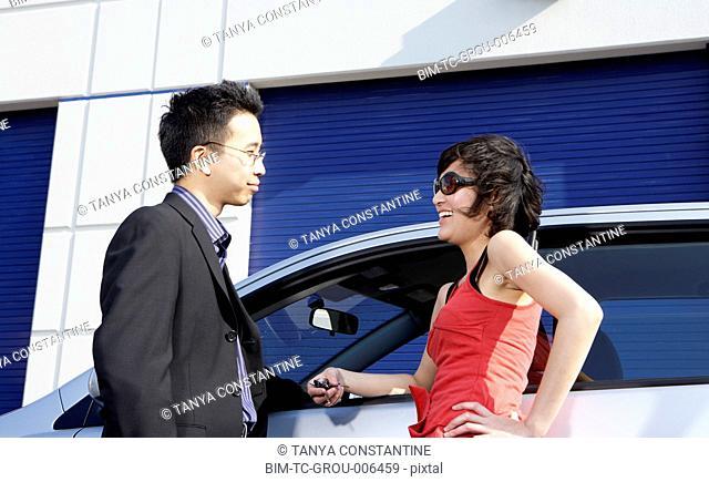 Asian businessman talking to woman next to car