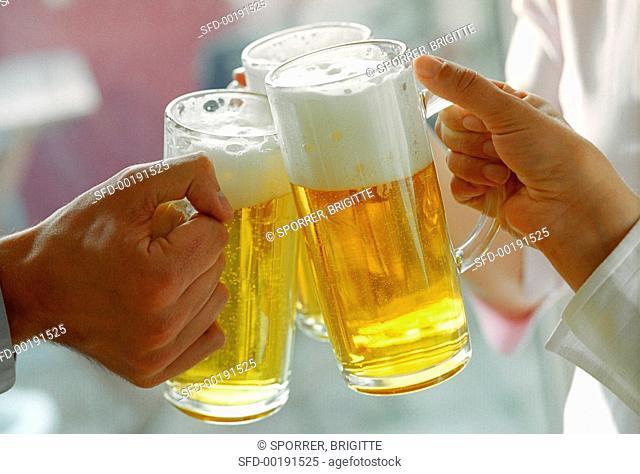 Hands clinking beer tankards (grainy effect)