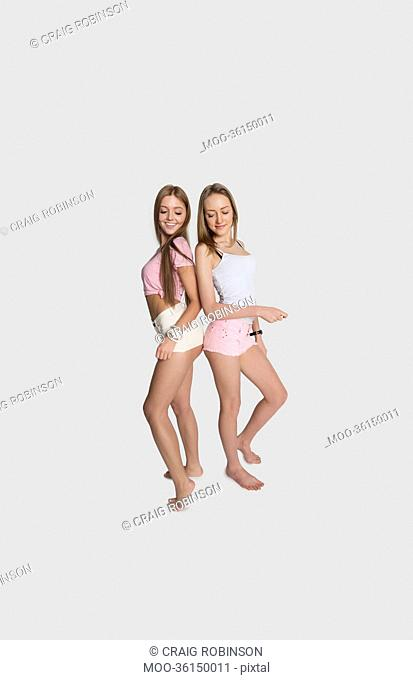 Full length of female friends wearing hot pants posing over gray background