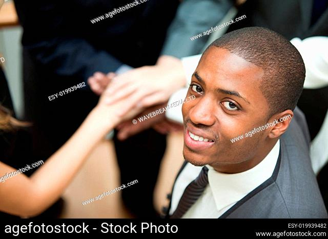 High view of hands together and a businessman smiling at the camera. Concept of