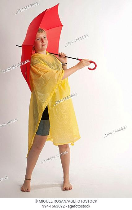 Teenage girl with yellow rain gear protected with red umbrella