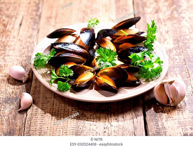 plate of mussels with parsley on wooden table