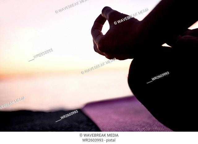 Mid section of woman performing yoga on beach
