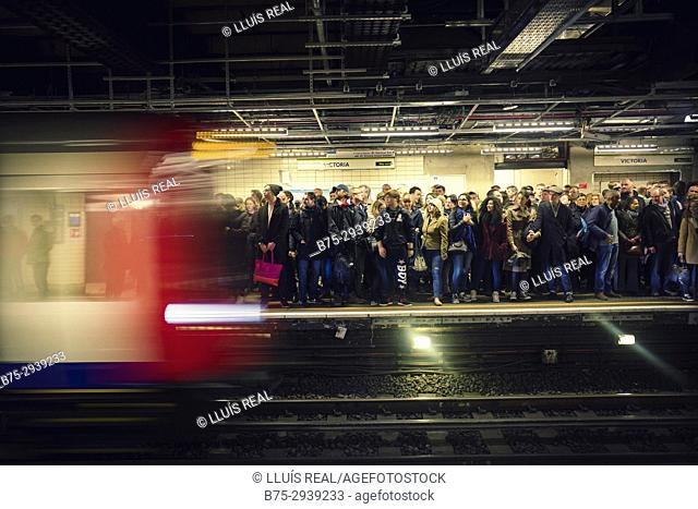 Crowd and moving train in Victoria Station. London, England