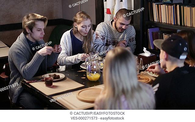 Hipster teenagers enjoying snack together in cafe