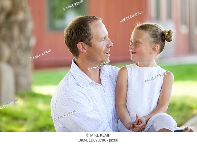 Caucasian father and daughter sitting together
