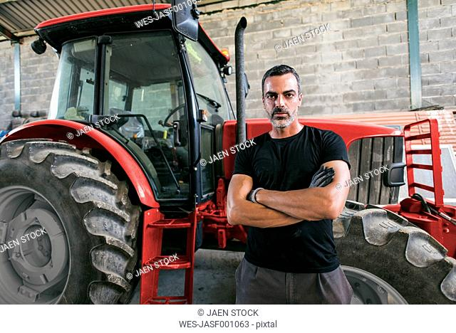 Portrait of confident mechanic at tractor