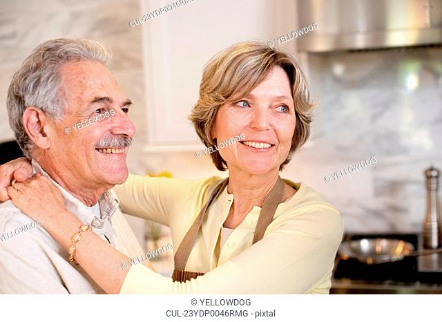 Smiling mature couple in kitchen
