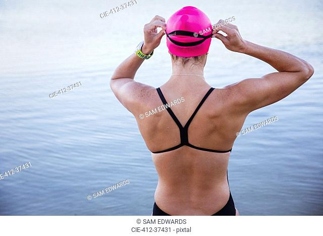 Female open water swimmer adjusting swimming goggles at ocean