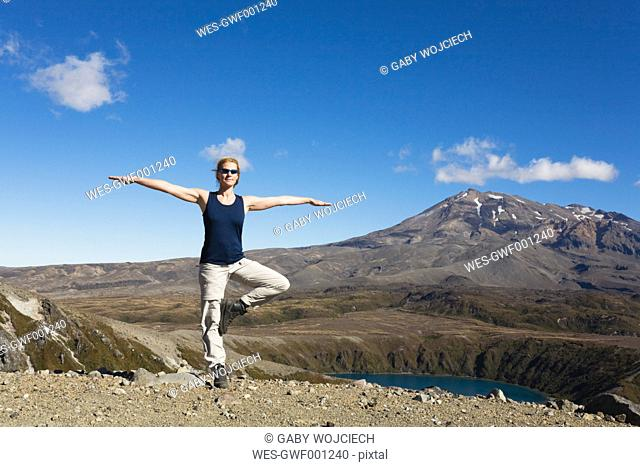 New Zealand, North Island, Woman doing exercise at tongariro national park with mount ruapehu in background