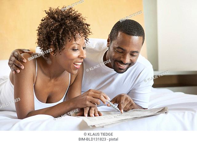 African American couple reading in bed