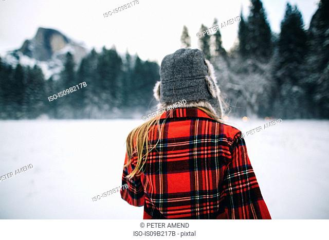 Woman wearing ushanka hat on snow-covered landscape