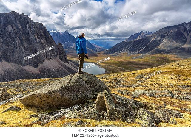 Man standing on a rock overlooking the granite peaks of Tombstone Territorial Park in autumn; Yukon, Canada