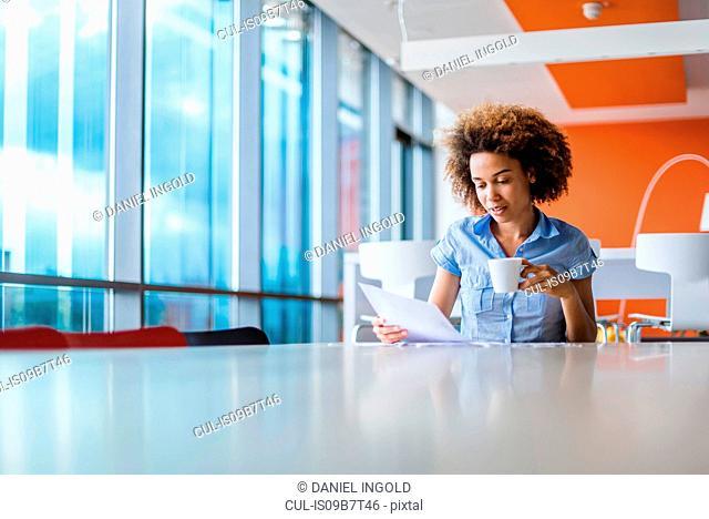 Young woman at table looking at paperwork