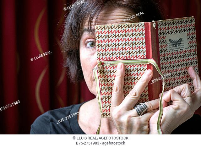 Middle-aged woman covering half face with an open book in her hands