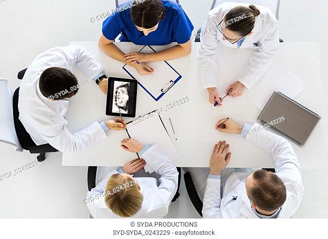 doctors with jaw x-ray on tablet pc at clinic