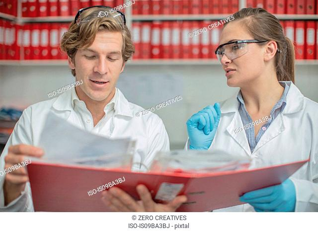Two lab workers, looking at folder of paperwork