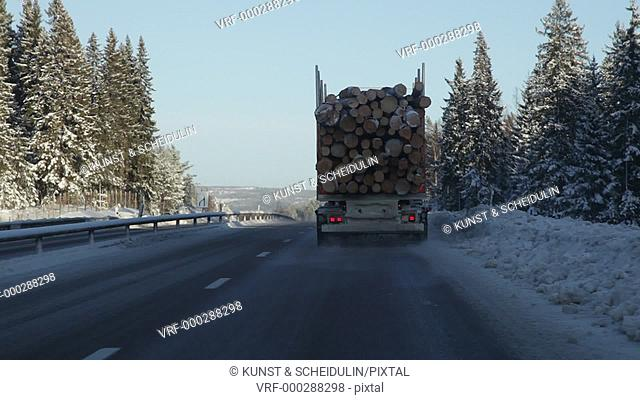 POV shot from a car that is following a timber truck on a motorway leading through a snowy forest on a bright winter day
