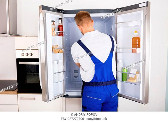 Young Male Repairman Fixing Refrigerator In Kitchen