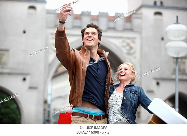 Mid adult couple taking selfie in front of Neuhauser Tor, Munich, Bavaria, Germany, Europe