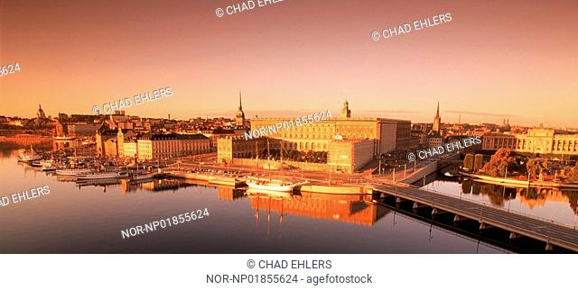 Boats moored along Skeppsbron with Royal Palace and Old Town in Stockholm at dawn