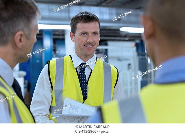 Workers in reflective clothing talking in factory