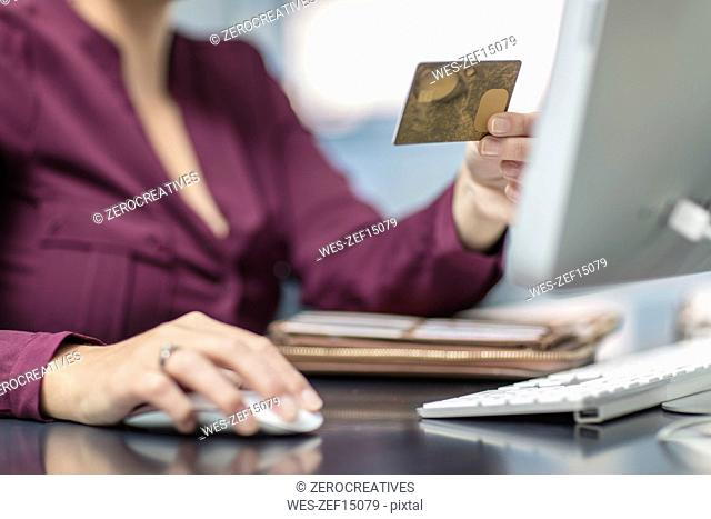 Businesswoman holding card at desk in office