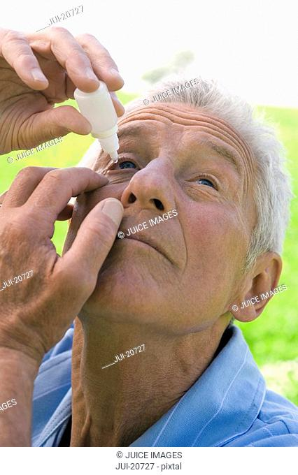 Senior woman using eye drops