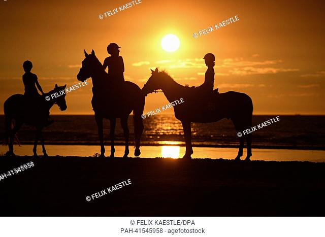 Three girls ride on the beach, while the sun sets in the background in De Panne, Belgium, 02 August 2013. Photo: Felix Kaestle | usage worldwide