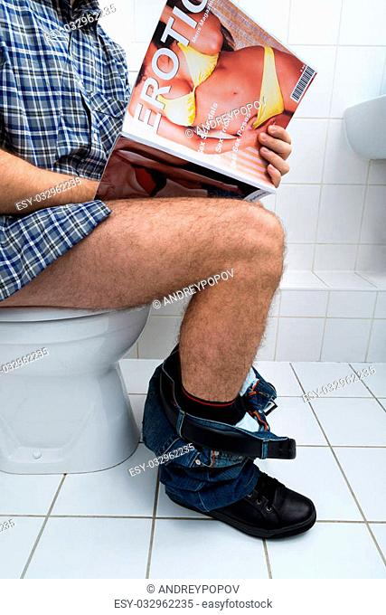 Close-up Of A Man Sitting On Commode Holding Sexy Magazine