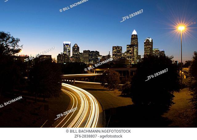 Charlotte North Carolina skyline at night with traffic blurs and twilight