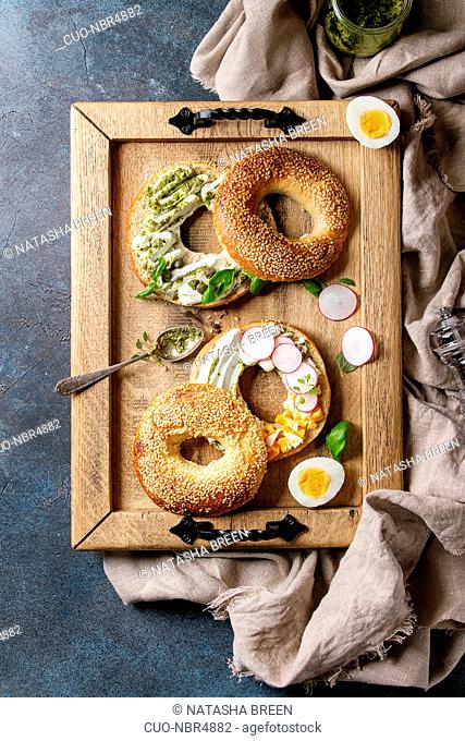 Variety of homemade bagels with sesame seeds, cream cheese, pesto sauce, eggs, radish, herbs served on wooden tray with cloth and ingredients above over blue...